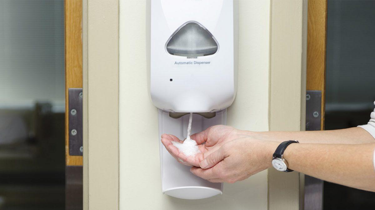 Using hand sanitizer on dispenser