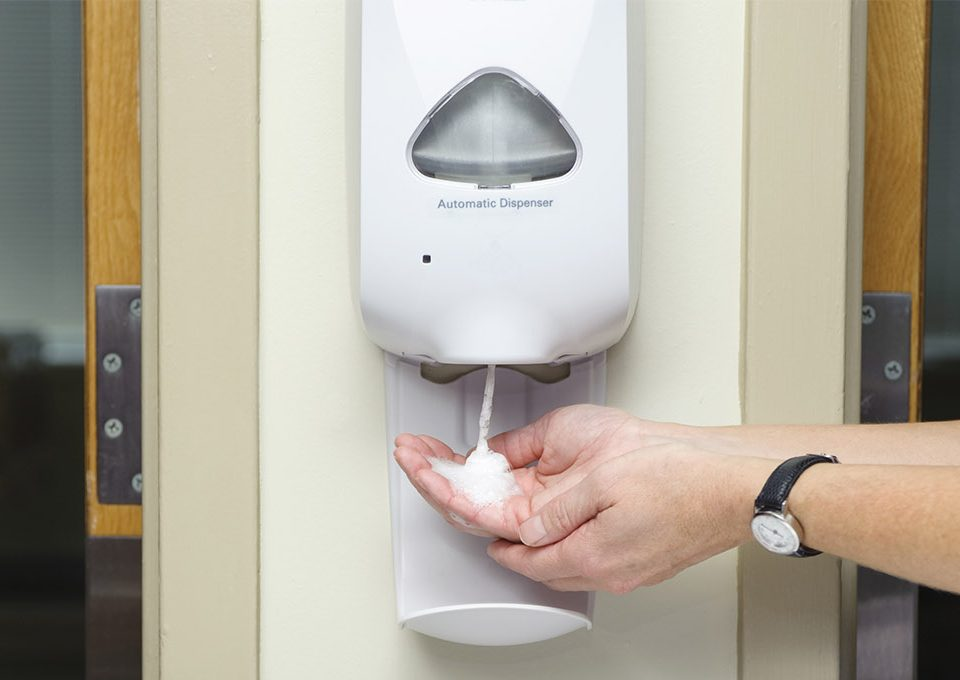 Using hand sanitizer on dispenser
